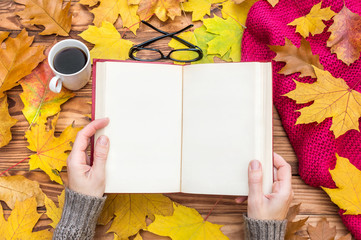 Woman reading  book on the table with autumn leaves, cup of coffee and knitted scarf. Space for text.