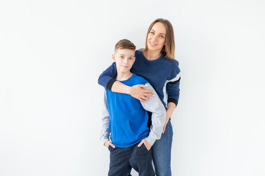 Parenting, family and single parent concept - A happy mother and teen son laughing and embracing on white background with copy space