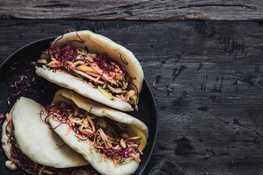 Steamed vegan bao buns with vegetables and peanuts.
