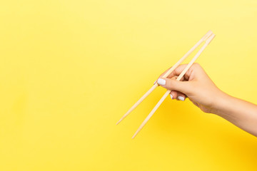 Girl's hand showing chopsticks on yellow background. Asian cuisine concept with empty space for your design Fototapete