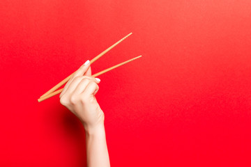 Creative image of wooden chopsticks in female hand on red background. Japanese and chinese food with copy space
