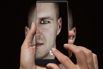 Woman taking pictures on cell phone a man's face with blue eyes and short hair and stubble beard on black background.