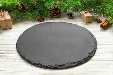 Perspective view. Empty black slate plate on wooden christmas background. holiday dinner dish concept with new year decor