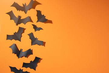Halloween picture of black bats flying up on blank orange background.