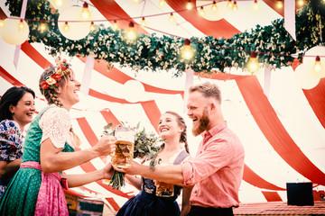 Fototapete - Gruppe von Freunden mit Bier auf dem Oktoberfest stoßen an mit Bier im Festzelt