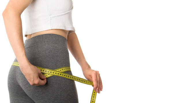 Woman measuring her body. Slim woman measuring her hips isolated on white background. Healthy nutrition and weight losing concept. Body fat reduction. Copy space.