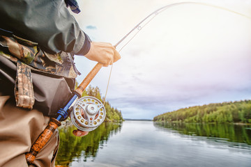 Fisherman spool of rope using rod fly fishing in river