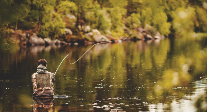Fisherman using rod fly fishing in river morning sunrise banner