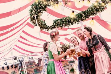 Fototapete - Gruppe von 5 Freunden auf dem Oktoberfest in Trachten stoßen mit Maß Bier an