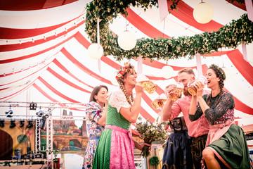 Fototapete - Gruppe von Freunden in Trachten und Dirndl auf der Regensburger Dult, Oktoberfest, Wiesn