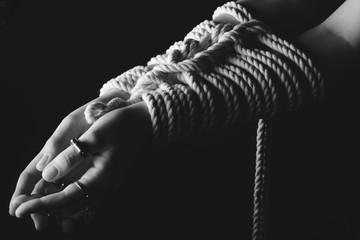 Kinbaku women's hands tied with rope