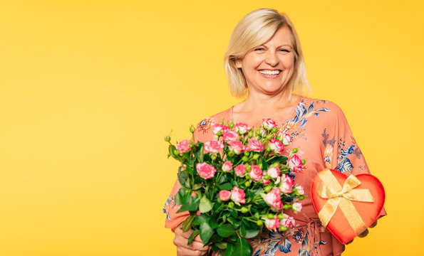 Holiday event. Mother's day. St. Valentines day. Birthday. Portrait of happy cute lovely senior woman in party colorful clothes with large bouquet of flowers on yellow background