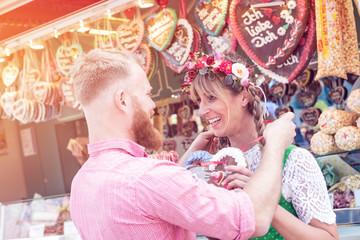 Fototapete - Junges verliebtes Paar mit Trachten vorm Lebkuchenherzen Stand auf der Dult