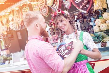 Fototapete - Pärchen auf der Dult, Mann kauft seiner Frau ein Lebkuchenherz