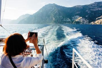 Tourist taking photos during cruise in Tyrrhenian Sea in Positano