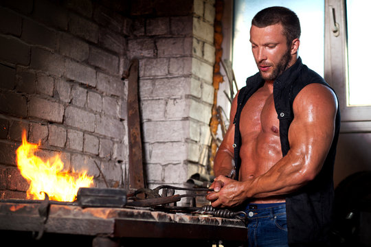 young sports man working in a forge