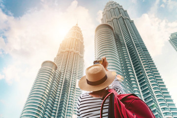 oung female tourist making picture shot of two Petronas towers skyscrapers in big asian Kuala Lumpur city, Malaysia