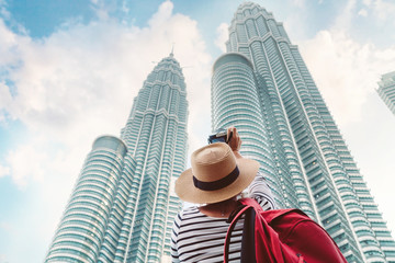 Young female tourist making picture shot of two Petronas Towers skyscrapers in Kuala Lumpur city,  Malaysia – MARCH 12, 2019