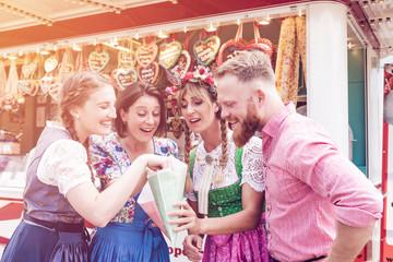 Fototapete - Gruppe von Oktoberfest Freunden vorm Stand essen Süßes und naschen