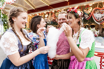 Fototapete - Gruppe von Volksfest Besuchern in Trachten nascht Zuckerwatte
