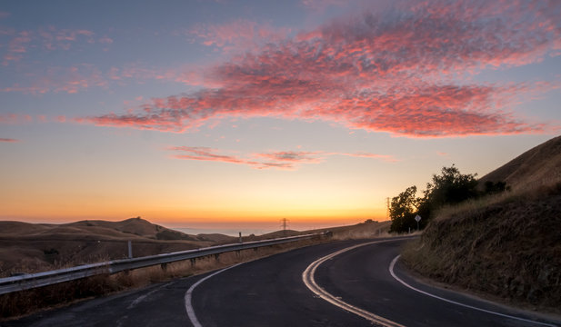 Shart Right Curve on Small Mountain Road With Coloful Sunset in the Background
