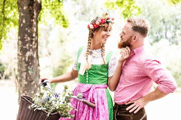 Fototapete - Junge verliebtes Paar mit Fahrrad auf dem Weg zur Festwiese in Trachten