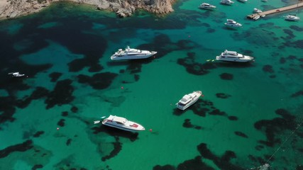 Wall Mural - View from above, stunning aerial view of a luxury yacht floating on an emerald green water in Sardinia. Maddalena Archipelago National Park, Sardinia, Italy.