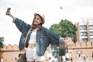 Smiling woman traveler in thapae gate landmark chiangmai thailand enjoy and arms raised with backpack on holiday, relaxation concept, travel concept