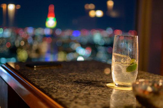 高級バー、飲みかけのカクテルと夜景