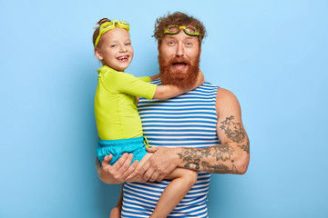 Photo of bearded young father wears goggles and striped vest, carries little daughter, spend summer holidays actively, enjoy swimming, love each other, isolated on blue background. Family concept