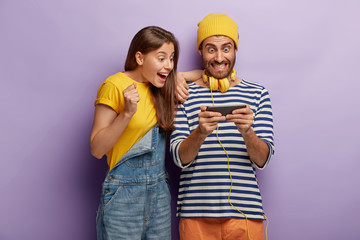 Happy girlfriend and boyfriend enjoy new game, being satisfied with new smartphone features, gaze at screen of gadget, dressed in fashionable clothes, cheering to win online marathon, being addicted