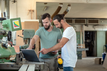 two worker in a carpenter's workshop with computer