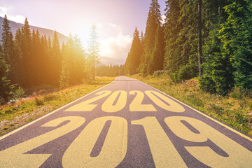 Empty asphalt road and New year 2020 concept. Driving on an empty road in the mountains to upcoming 2020 and leaving behind old 2019. Concept for success and passing time. Wall mural