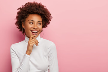 Satisfied carefree female model smiles gently, touches chin, looks aside, notices funny scene, laughs at something, has natural curly dark hair, dressed casually, isolated on pink background