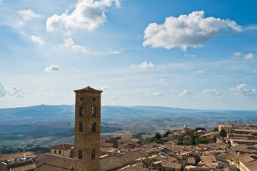 Cityscape over the roofs and surrounding landscape with bell tower of Volterra duomo in front, Tuscany, Italy