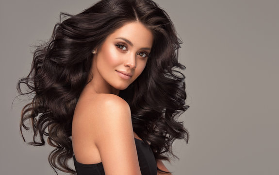 Beauty brunette girl with long  and   shiny wavy black hair .  Beautiful   woman model with curly hairstyle .