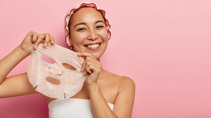 Attractive young chinese woman applies paper sheet mask on face, enjoys beauty skin care, stands wrapped in towel, wears bath cap, smiles positively, isolated on pink background. Rejuvenation concept