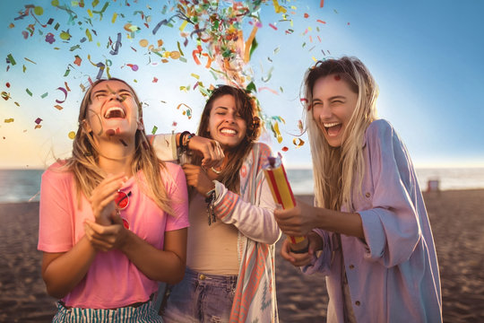 Happy young people having fun at beach party, celebrating with confetti.