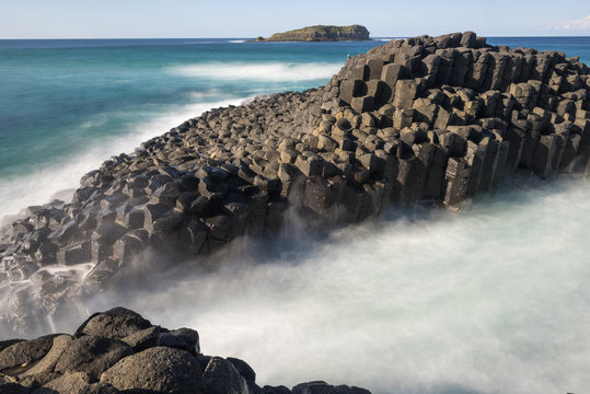 Black, basalt columns on a small island just off the tip of Fingal Head in New South Wales, Australia. A slow shutter speed captures the swirling white water between the island and the mainland.
