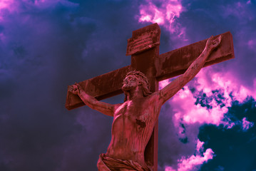 Crucifix lit by red bloody light against a dramatic sky with purple hues