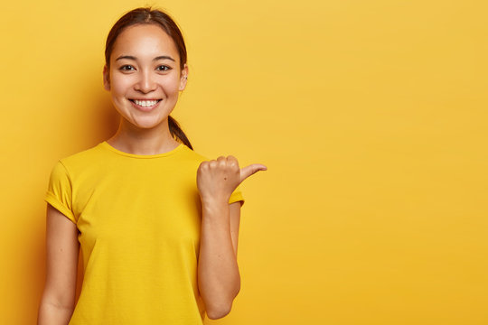 Studio portrait of young cheerful Asian female points away with thumb, happy face expression, demonstrates copy space for advertisement, has pleasant appearance, wears bright yellow clothes.