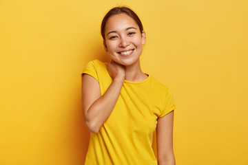 Charming Asian woman has cheerful expression, touches neck and tilts head, has pleasant talk with interlocutor, hears pleasant news, wears vivid casual t shirt, isolated on yellow background