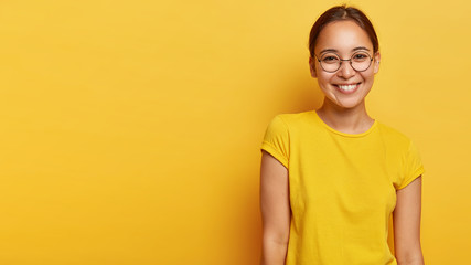 Photo of pleased happy Asian woman has gentle smile, shows white teeth, wears eyewear and yellow t shirt, expresses positive emotions, poses indoor with blank space for your promotional content
