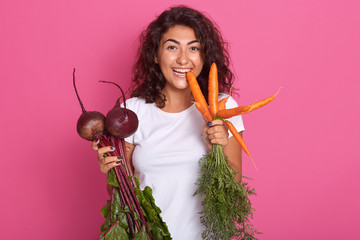 Image of young woman with dark wavy hair dressed white casual t shirt holding beets and carrots in hands, looking directly at camera, biting carrot. Raw food diet and healthy eating concept.