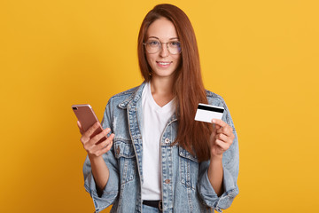 Image of attractive woman holding cell phone and credit card in hands, female wering denim jacket, white t shirt, spectacles, posing isolated over yellow background. Online shopping concept.