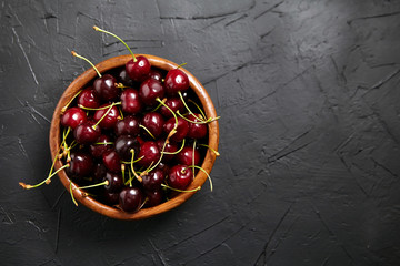 Türaufkleber Kirschblüte Ripe cherries in a wooden bowl on a black stone table. Red berries on a dark background with copy space, top view