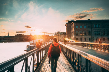 Stockholm, Sweden. Young Caucasian Woman Lady Tourist Traveler Walking On Famous Skeppsholmsbron - Skeppsholm Bridge. Popular Place, Landmark And Destination In Stockholm, Sweden