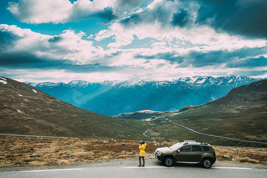 Aurlandsfjellet, Norway. Young Caucasian Woman Lady Tourist Traveler Photographer Taking Pictures Photos Near Parked Car. Aurlandsfjellet Scenic Route Road In Summer Norwegian Countryside Landscape