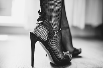 sexy woman legs in high heel sandals. fishnet stockings with black bow.