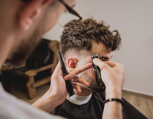 Papiers peints Salon de coiffure Young man with trendy haircut at barber shop. Barber does the hairstyle and beard trim.